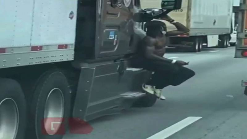 Video footage shows a man riding on the outside of a semitruck on a Georgia interstate.