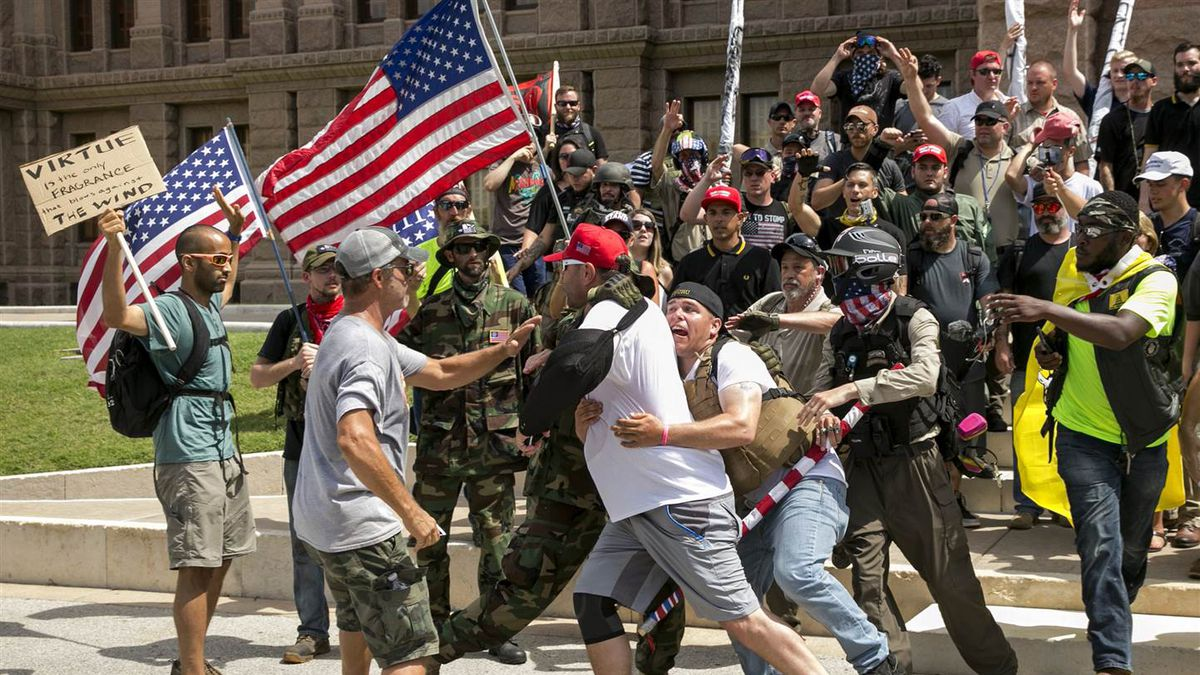 Kyle Chapman is held back by his fellow Trump supporters from confronting Trump protester Nevin Kamath, far left, at the impeachment march at the Capitol in Austin, Texas, on July 2. (Jay Janner / Austin American-Statesman via AP)