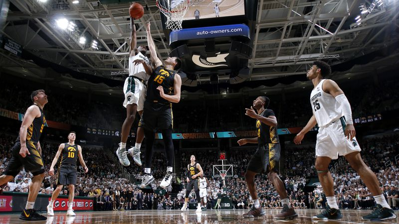 Michigan State's Aaron Henry, top left, goes up for a shot against Iowa's Ryan Kriener (15)...