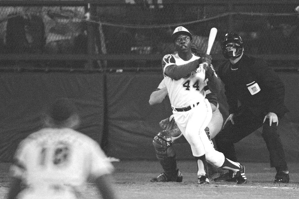 Atlanta Braves' Hank Aaron eyes the flight of the ball after hitting his 715th career homer in...