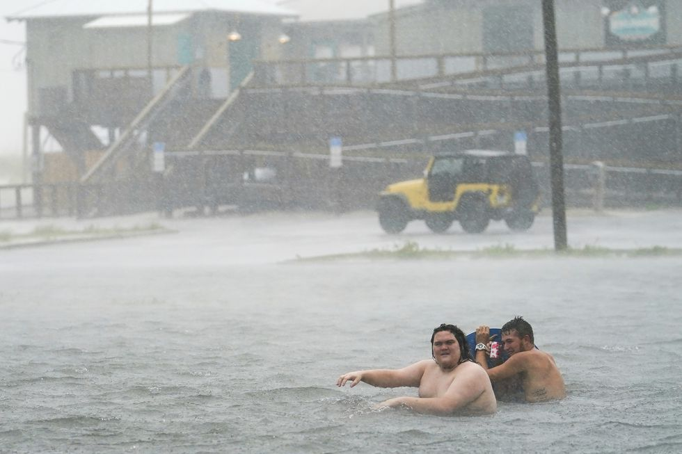 People play in a flooded parking lot at Navarre Beach, Tuesday, Sept. 15, 2020, in Pensacola Beach, Fla. Hurricane Sally is crawling toward the northern Gulf Coast at just 2 mph, a pace that's enabling the storm to gather huge amounts of water to eventually dump on land.