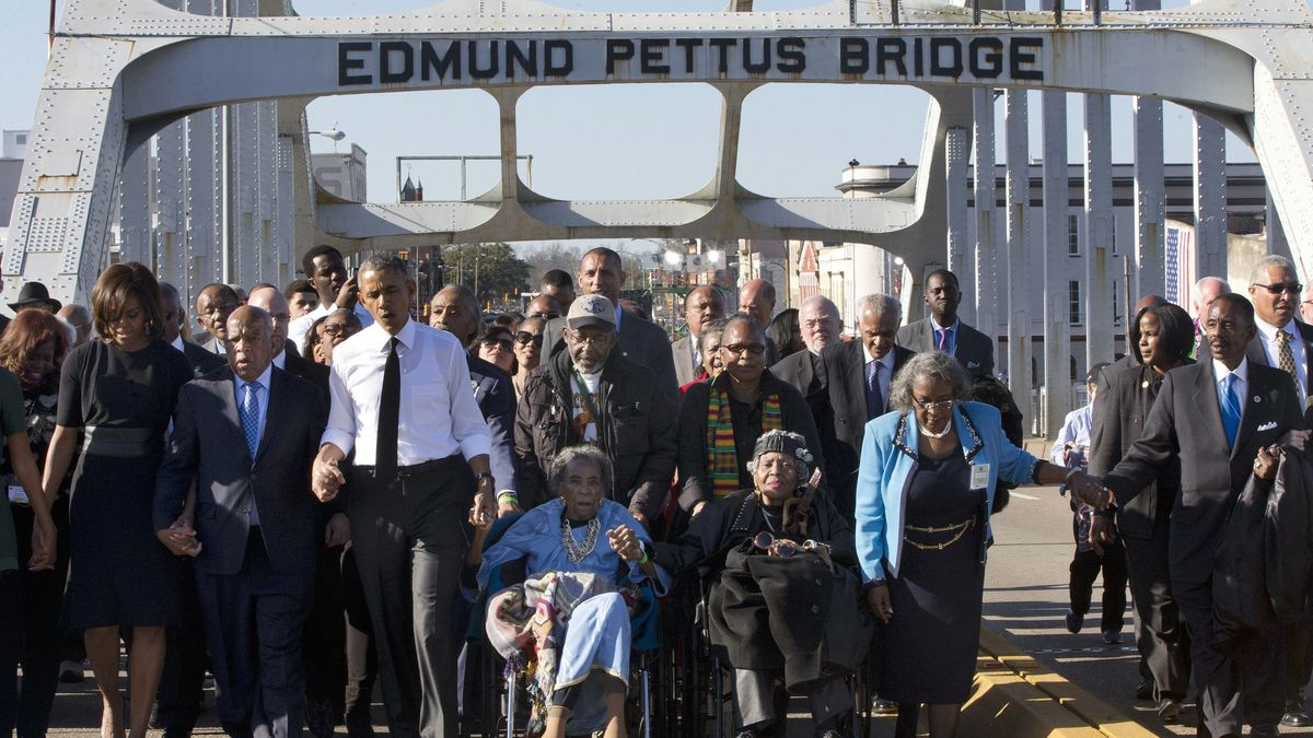 """In this March 7, 2015, file photo, singing """"We Shall Overcome,"""" President Barack Obama, third from left, walks holding hands with Amelia Boynton, who was beaten during """"Bloody Sunday,"""" as they and the first family and others including Rep. John Lewis, D-Ga, left of Obama, walk across the Edmund Pettus Bridge in Selma, Ala., for the 50th anniversary of """"Bloody Sunday,"""" a landmark event of the civil rights movement. Some residents in the landmark civil rights city of Selma, Ala., are among the critics of a bid to rename the historic bridge where voting rights marchers were beaten in 1965."""