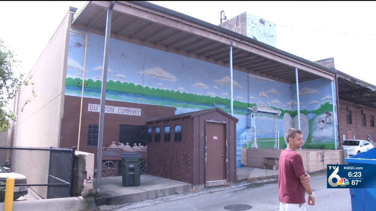 Painter Chris Anderson of Muscatine stands in front of his mural at the National Pearl Button Museum. (KWQC)