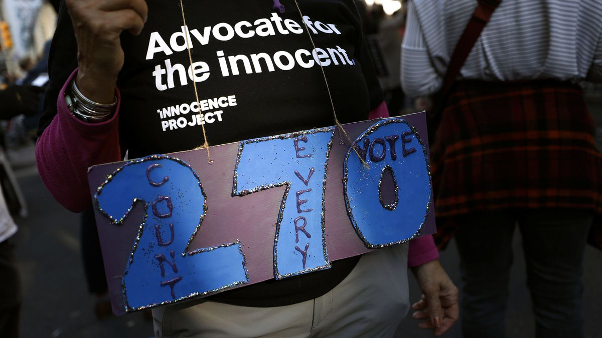 A person holds a sign referring to the number of electoral votes needed to win the presidency...