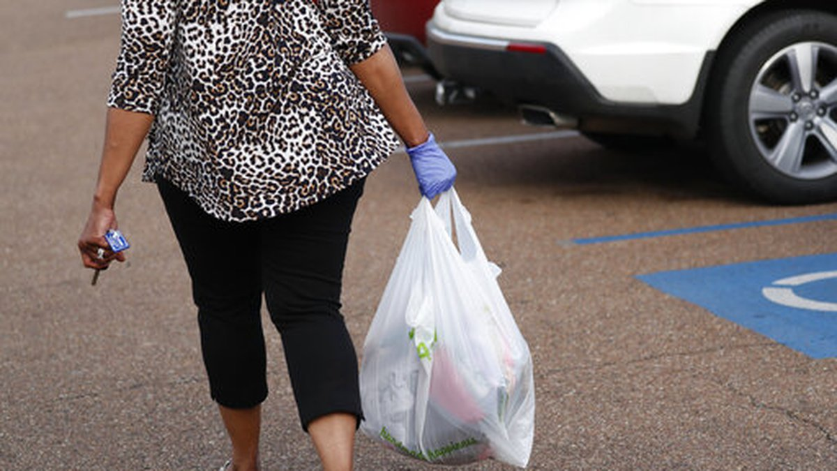 A gloved shopper carries her purchases through the Target parking lot in northeast Jackson,...