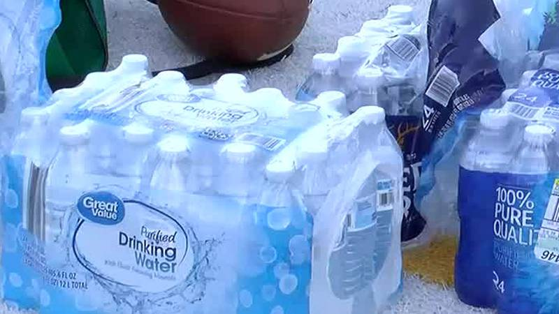 Parents brought in cases of bottled water for a Charlotte high school football team following...