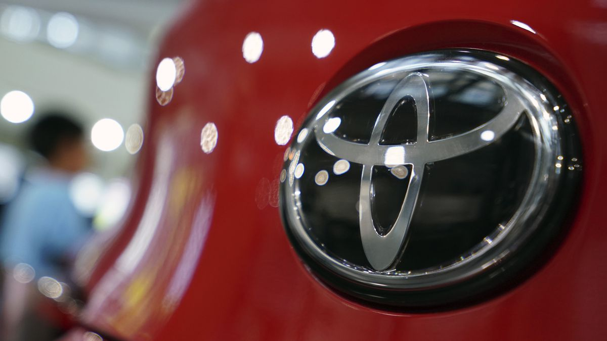 FILE - In this Aug. 2, 2019 file photo, people walk by the logo of Toyota at a show room in...