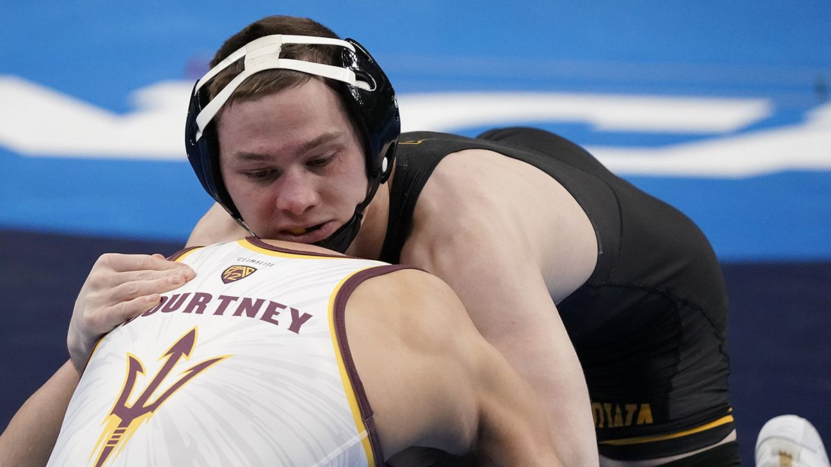 Iowa's Spencer Lee, top, takes on Arizona State's Brandon Courtney during their 125-pound match...