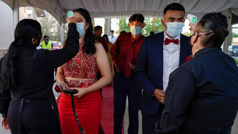 Grace Gardens Event Center employees check temperatures of young people attending prom at the...