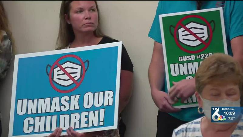 """Over 30 people showed up to the Board of Education meeting holding signs saying, """"unmask our..."""