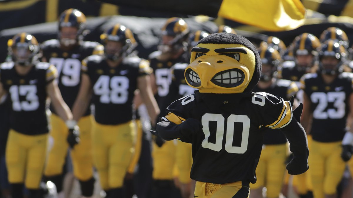 The Iowa Hawkeyes mascot runs onto the field, leading the team before the start of an NCAA...