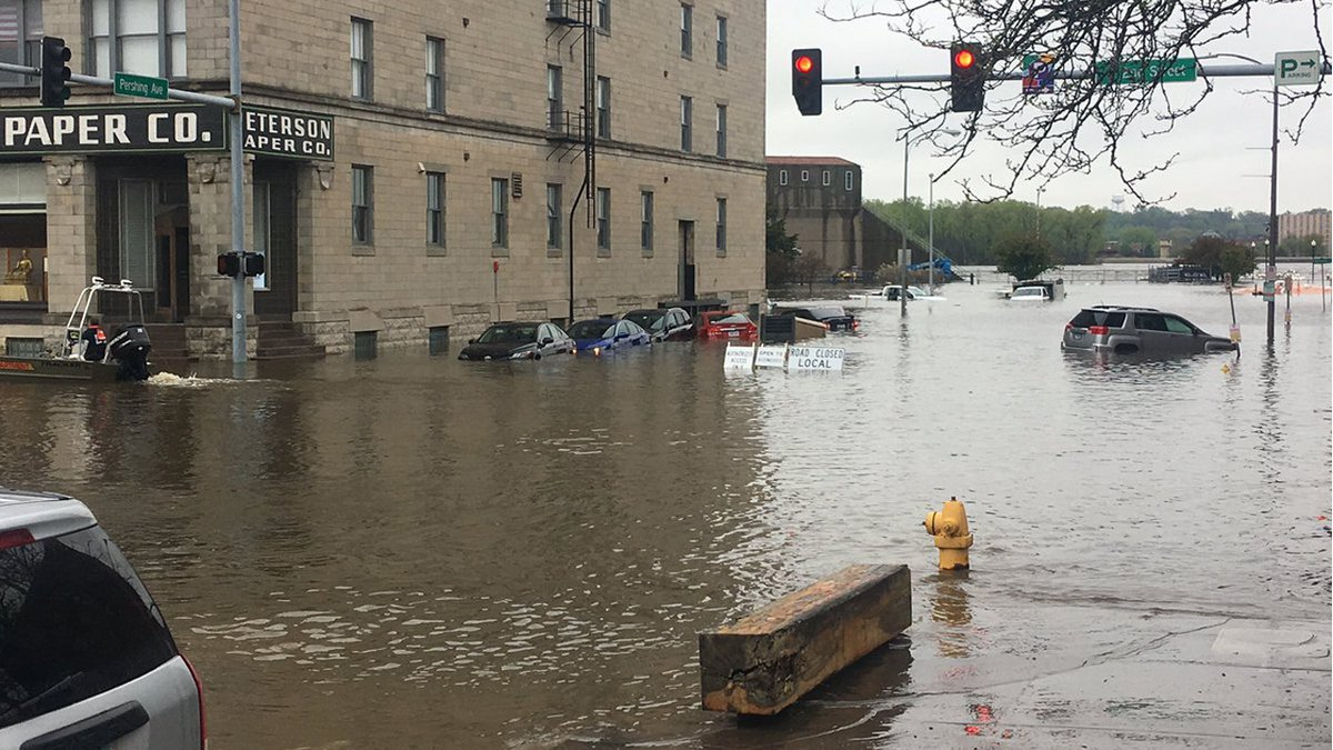 Water inundates cars and roadways near 2nd Street and Pershing Avenue in downtown Davenport on...