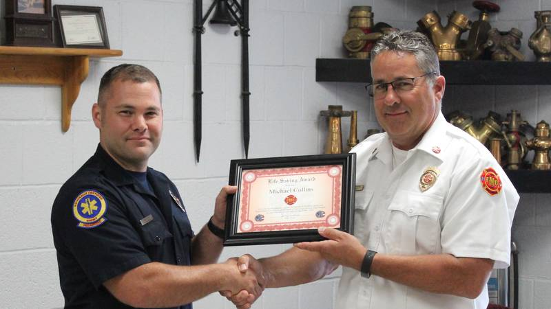 Firefighter Mike Collins (left) is given the Life Saving Award by Fire Chief Jerry Ewers.
