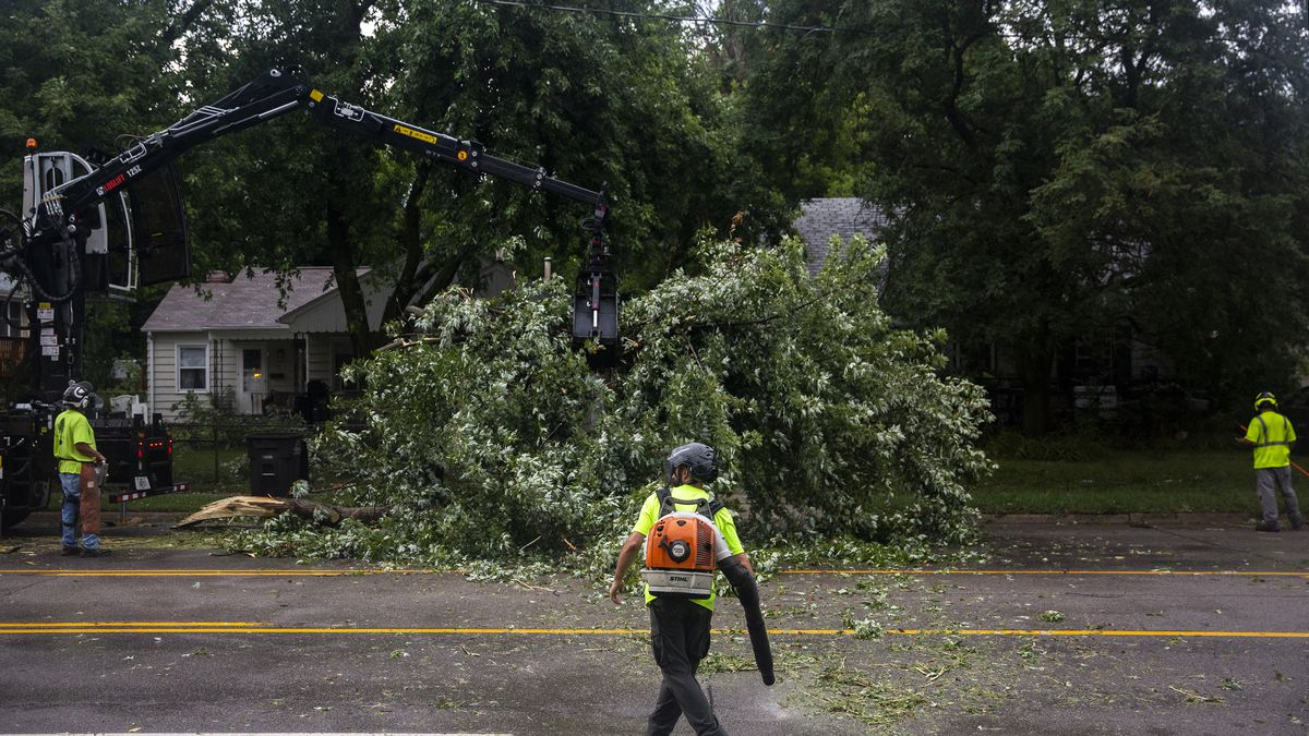 Des Moines city crews remove a tree fallen on Hickman Road, on Monday, Aug. 10, 2020, in Des Moines, Iowa after a storm with gusts more than 80 mph blew through the city.