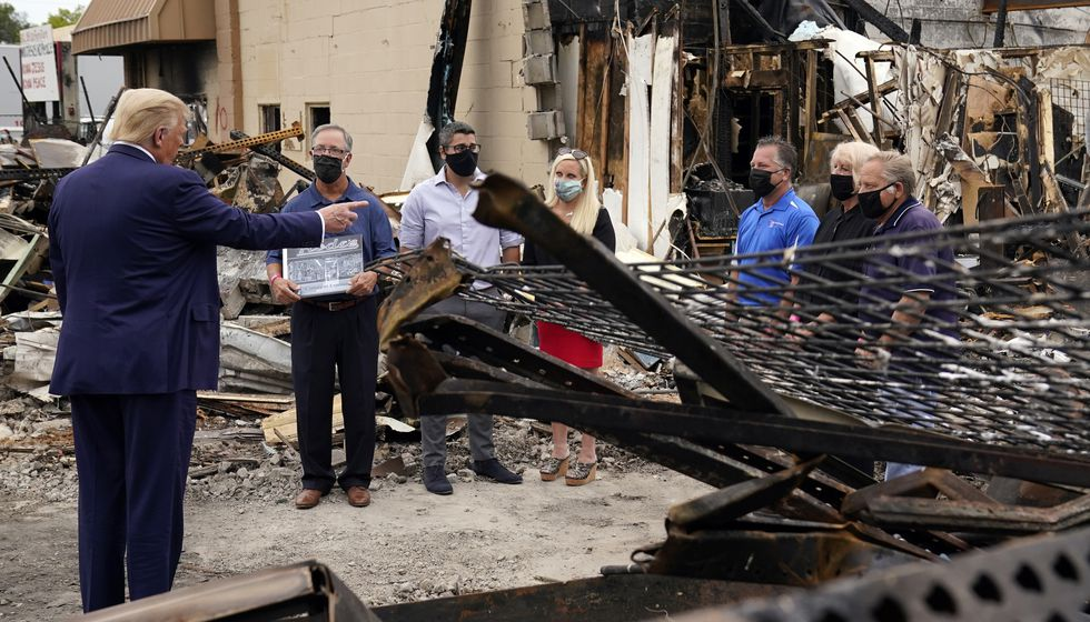 President Donald Trump talks to business owners Tuesday, Sept. 1, 2020, as he tours an area damaged during demonstrations after a police officer shot Jacob Blake in Kenosha, Wis.