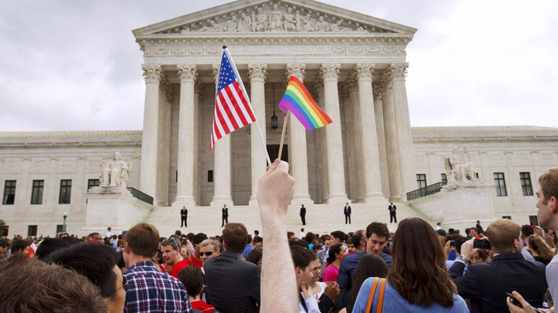 FILE - In this June 26, 2015 file photo, a man holds a U.S. and a rainbow flag outside the...