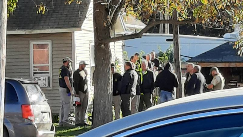 Law enforcement officials gather outside of a home in New Sharon where a search warrant in a...